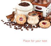 Cup of fragrant coffee, the coffee grinder, coffee grains in a knitted bag and cookies on a white background. — Stock Photo