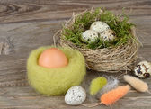 Easter eggs in nests and feathers on a wooden background. Easter background. — Stock Photo