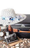 Old suitcase, the camera and hat on a white background. Retro travel. — Stock Photo