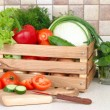The fresh washed-up vegetables in a wooden box and the cut vegetables on a chopping board against modern kitchen. — Stock Photo #65781991
