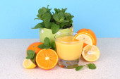 Glass of orange juice both various citruses and mint on a table on a blue background. — Stock Photo