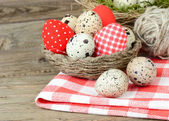 Easter background with quail and textile eggs in a nest. — Stock Photo