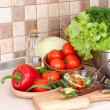 The fresh washed-up vegetables in a colander and the cut vegetables on a chopping board against modern kitchen. — Stock Photo #65855317