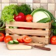 The fresh washed-up vegetables in a wooden box and the cut vegetables on a chopping board against modern kitchen. — Stock Photo #65855347