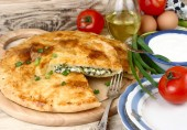 The fresh baked house pie with a stuffing from eggs and green onions it is also swept away in a retro plates on wooden a rustic a background. — Stock Photo
