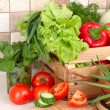 The fresh washed-up vegetables in a wooden box and the cut vegetables on a chopping board against modern kitchen. — Stock Photo #65954313