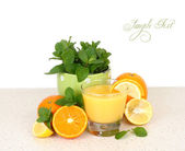 Glass of orange juice both various citruses and mint on a table on a white background. — Stock Photo