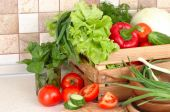 The fresh washed-up vegetables in a wooden box and the cut vegetables on a chopping board against modern kitchen. — Stock Photo