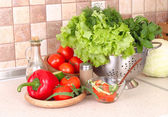 The fresh washed-up vegetables in a colander and the cut vegetables on a chopping board against modern kitchen. — Stock Photo