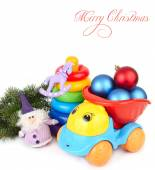 Christmas balls by children's toy car and a pyramid on a white background. Christmas background. — Stock Photo