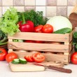 The fresh washed-up vegetables in a wooden box and the cut vegetables on a chopping board against modern kitchen. — Stock Photo #66387297