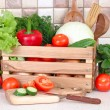 The fresh washed-up vegetables in a wooden box and the cut vegetables on a chopping board against modern kitchen. — Stock Photo #66506881