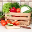 The fresh washed-up vegetables in a wooden box and the cut vegetables on a chopping board against modern kitchen. — Stock Photo #66507041