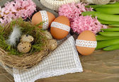 Easter eggs on a cretaceous board, a nest and hyacinths on a wooden background. Easter background. — Stock Photo