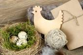 Easter eggs in a nest and wooden chicken on a wooden background. Easter background. — Stock Photo