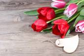 Fresh tulips and heart on a wooden background. Flowers for lovers. — Stock Photo