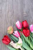 Tulips, Easter egg and wooden chicken on a wooden background. Easter background. Top view. — Stock Photo