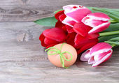Bouquet of fresh tulips, Easter egg and wooden chicken on wooden a rustic a background. Easter background. — Stock Photo
