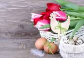 Bouquet of fresh tulips in a basket and Easter eggs in a knitted bag on wooden a rustic a background. Easter background. — Stock Photo