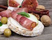 Ham slices with a fig and olives on grain small loafs on a wooden background. — Stock Photo