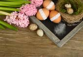 Pink hyacinths and Easter eggs on a blackboard (a cretaceous board) on wooden a rustic a background. Easter background. — Stock Photo