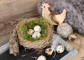 Easter eggs in a nest on a cretaceous board (blackboard) and wooden chicken on wooden a rustic a background. Easter background. — Stock Photo