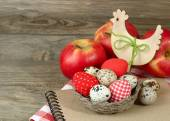 Textile and quail Easter eggs in a nest and wooden chicken on a wooden background. Easter background. — Stock Photo