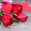 Bouquet of fresh red tulips and two red cardboard hearts on a wooden background. — Foto Stock #68225177