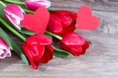 Bouquet of fresh red tulips and two red cardboard hearts on a wooden background. — Stock Photo