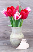 Tulips in a clay vase and wooden heart (a place for the text) on a rustic a wooden background. — Fotografia Stock