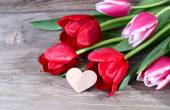 Bouquet of fresh red tulips and wooden heart (a place for the text) on a wooden background. — Stock Photo