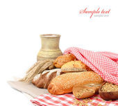 Fresh fragrant home-made bread under a checkered napkin and a jug with milk on a white background. — Stock Photo