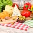 Cheese of various grades, fresh vegetables and olives on a light wooden background. Ingredients for preparation of the Italian vegetarian pizza. — Stock Photo #71157101