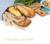 Fresh home-made bread under a blue linen napkin with ears and grain on a white background. — Stock Photo