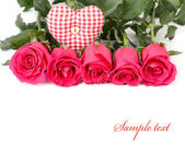 Pink roses and checkered heart on a white background. — Stock Photo