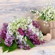"Charming spring flowers of a lilac and lilies of the valley and gift boxes on a wooden background. A background for the subject ""holiday"" with space for the text. — Stock Photo #73082645"