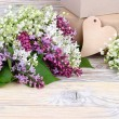 "Charming spring flowers of a lilac and lilies of the valley and gift boxes on a wooden background. A background for the subject ""holiday"" with space for the text. — Stock Photo #73082753"
