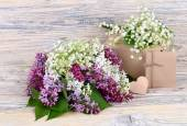 "Charming spring flowers of a lilac and lilies of the valley and gift boxes on a wooden background. A background for the subject ""holiday"" with space for the text. — Stock Photo"