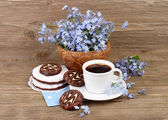 Cup of fresh fragrant coffee with cookies and a bouquet of field forget-me-nots on a wooden background. — Stock Photo