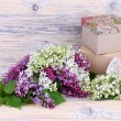 "Bouquets of a lilac and lilies of the valley and gift boxes on a wooden background. A background to the subject ""holiday"". — Stock Photo #73352565"