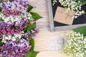 Flower background with a lilac, lilies of the valley and a cretaceous board with a place for the text. Top view. — Stock Photo