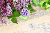 "Flower wooden background with a lilac, a gift box and tapes with a place for the text. Top view. A background to the subject ""holiday"". — Stock Photo"