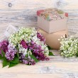 Flower wooden background with a lilac, lilies of the valley and gift boxes with a place for the text. — Stock Photo #73528397