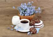 Cup of coffee with cookies and a bouquet of blue wild flowers on a wooden background with a place for the text. — Stock Photo