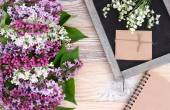 Flower wooden background with a lilac and a cretaceous board with a place for the text. Top view. — Stock Photo