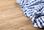 Blue checkered towel on a wooden background. — Stock Photo