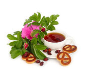 Tea with a dogrose, flowers and hips on a white background. — Stock Photo