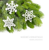 Fluffy branches of a Christmas tree and knitted white snowflakes on a white background. A Christmas background with a place for the text. — Stok fotoğraf