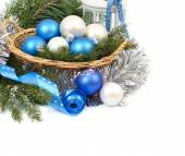 Blue and white Christmas balls in korizine silvery tinsel on a white background. Christmas composition with blue Christmas balls, cones and silvery snowflakes on a blue background. A Christmas background with a place for the text. — Stock Photo