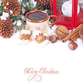 Cup of tea, ginger cookies and nuts near branches of a Christmas tree and cones on snow on a white background. A Christmas background with a place for the text. — Stock Photo